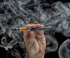 34581221 - hand holding an electronic cigarette over a dark background